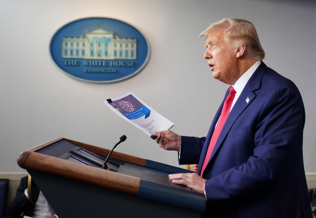 US President Donald Trump holds a Covid-19 vaccine playbook and distribution plan during a press conference in the Brady Briefing Room of the White House on September 16, 2020, in Washington, DC.