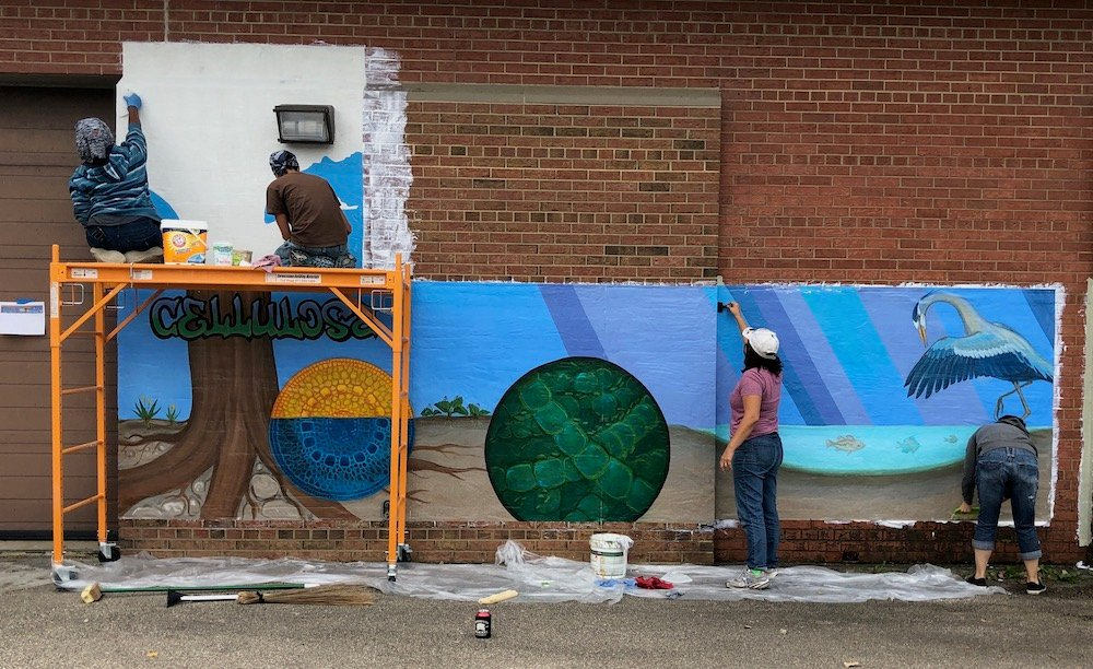 Artists work on incomplete mural of molecular structure