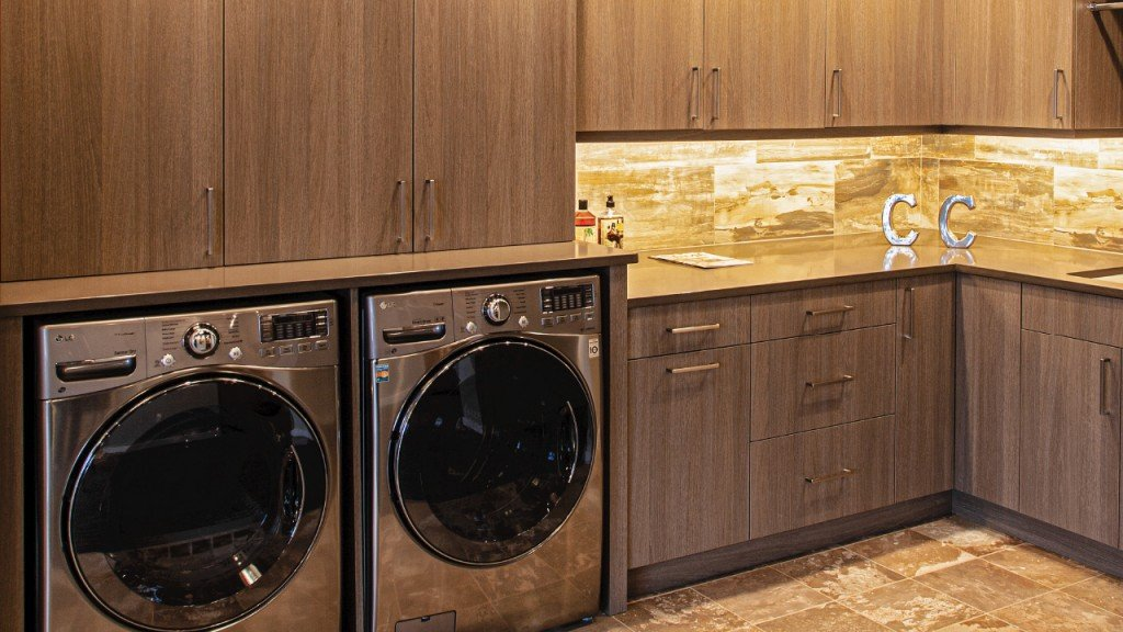 Interior of a laundry room with cabinets and drawers and a sink for organizing the room. Cabinets are made with warm wood tones with a tile backsplash and tile floors in a matching tone.