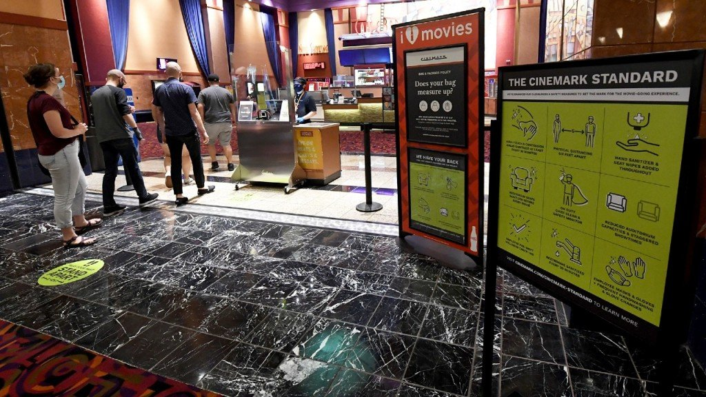 Customers Line Up Near A Sign Displaying New Safety And Cleaning Procedures At Cinemark's Century 16 At The South Point Hotel Casino In Las Vegas