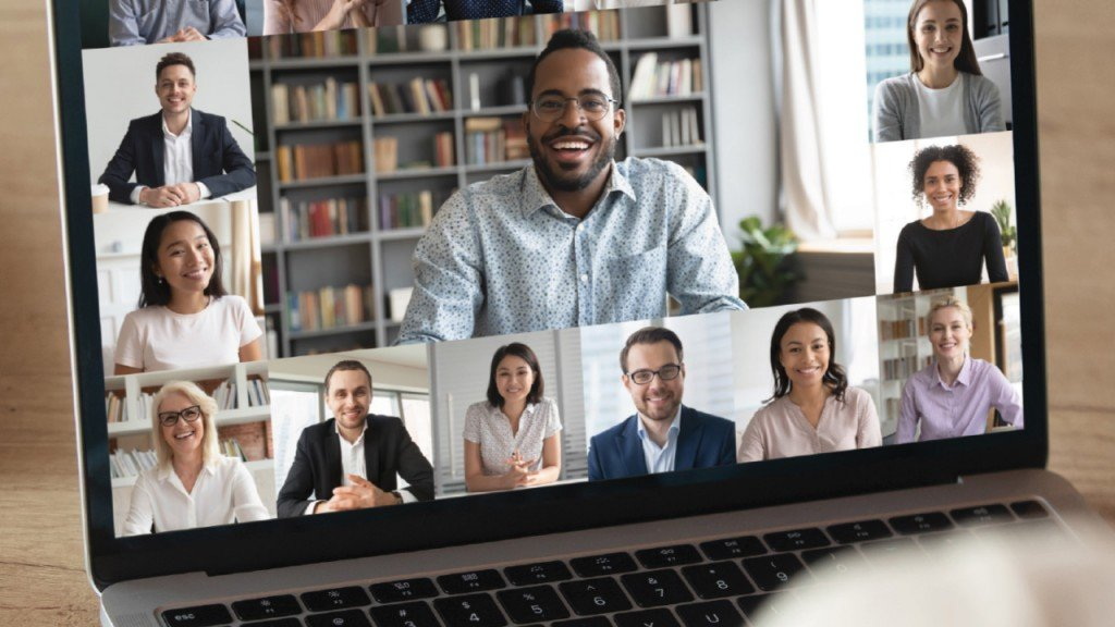 Laptop computer with a group of diverse people on a zoom call and a larger image of a host in the group.