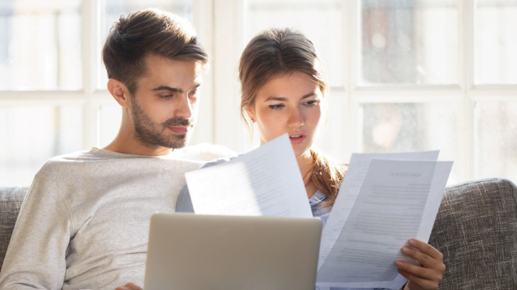 Photo of young serious millennial couple reading paperwork together with laptop open