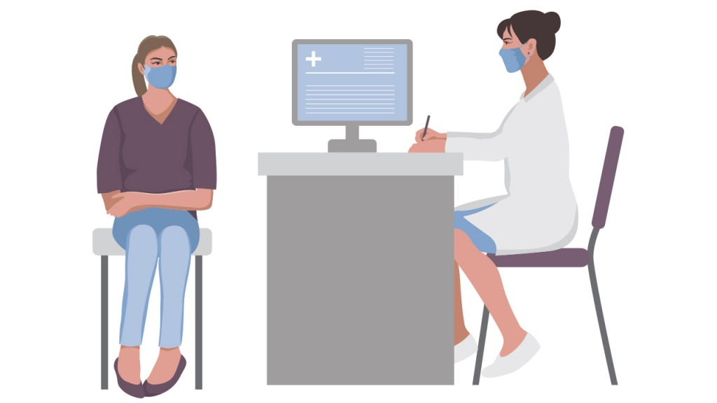 This image is of a female doctor at her desk with a computer that has generic copy on the screen and she is consulting with a patient who is sitting on the other side of the desk. They are both wearing masks.