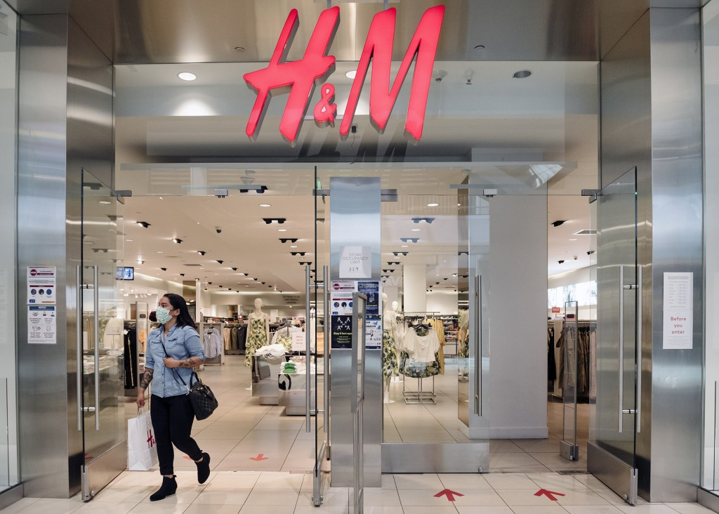 A shopper wearing a protective mask walks out of h&m