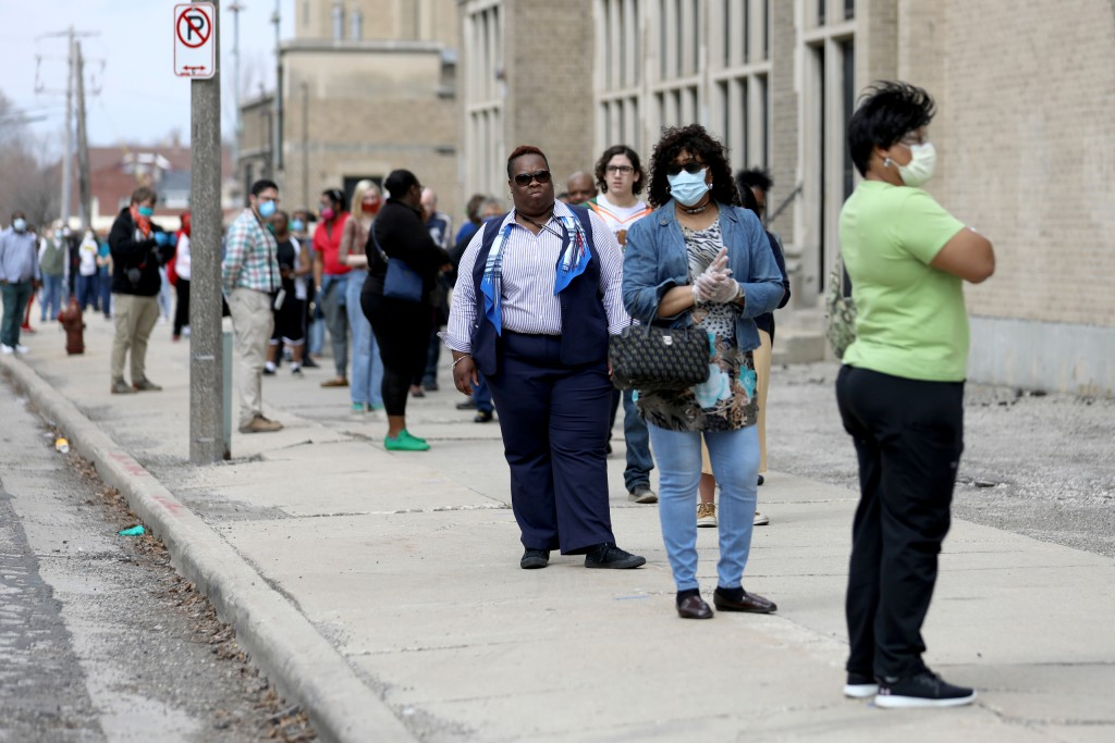 "A line of voters wraps around the block outside Washington High School in Milwaukee during the primary election on April 7, 2020. A top civil rights advocate called Wisconsin's election a ""travesty that put voters in the crosshairs of having to choose between their safety and their vote."" Various lawsuits are seeking a relaxation of Wisconsin's voting laws ahead of the Nov. 3 election due to the pandemic."