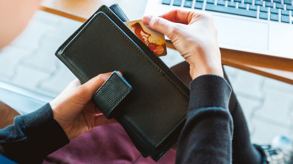 Person Taking Credit Card Out Of Wallet while online shopping