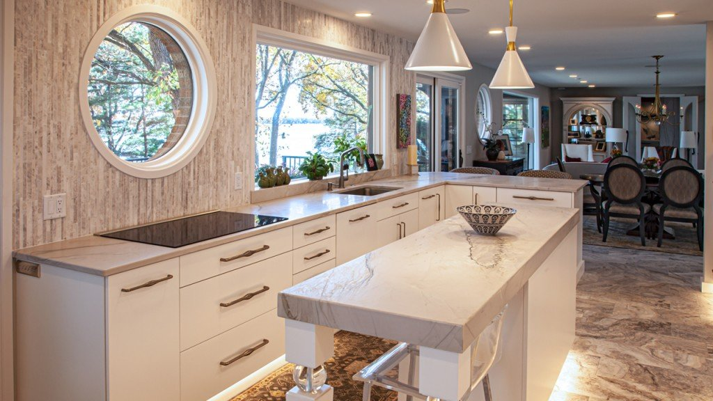Dream House designed Kitchen with white cabinetry and a white and gray marble statement island.