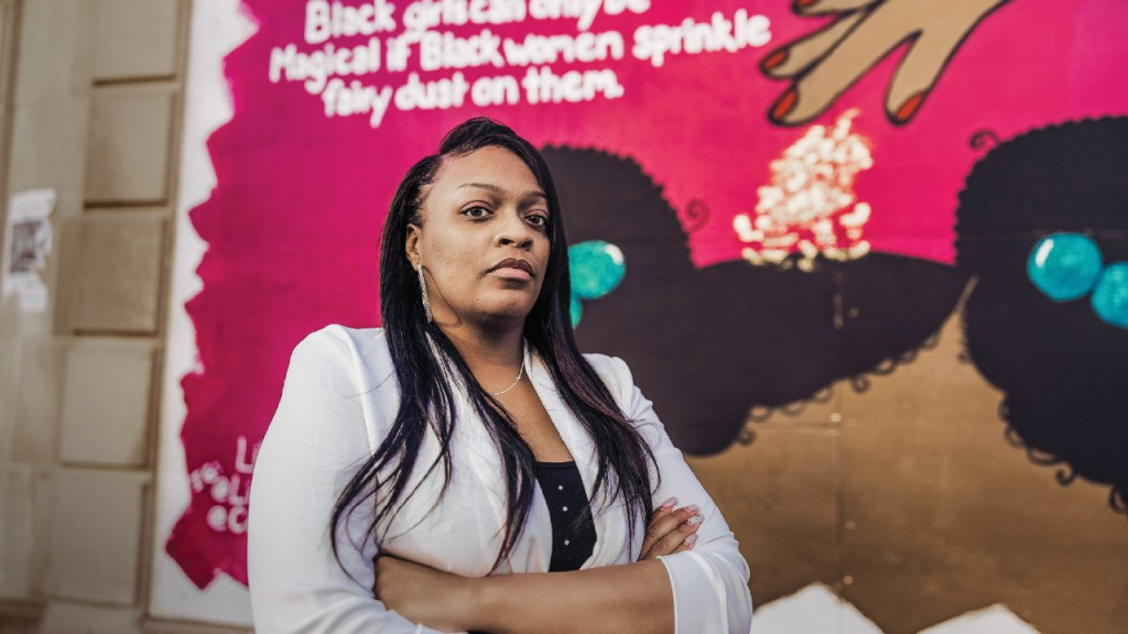 Ruby Clay in front of a mural about Black girls
