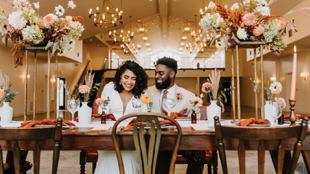 Gloria Oyervides and Montel Caruthers in an extravagant venue with flowers everywhere