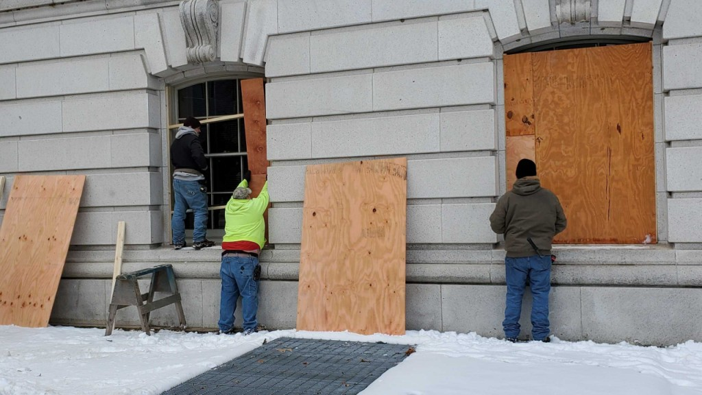 Crews install boards over the windows of the Wisconsin State Capitol on January 11th, 2021