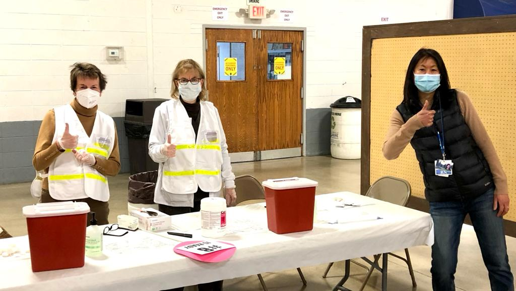 Workers at a Jefferson County vaccination clinic give a thumbs up