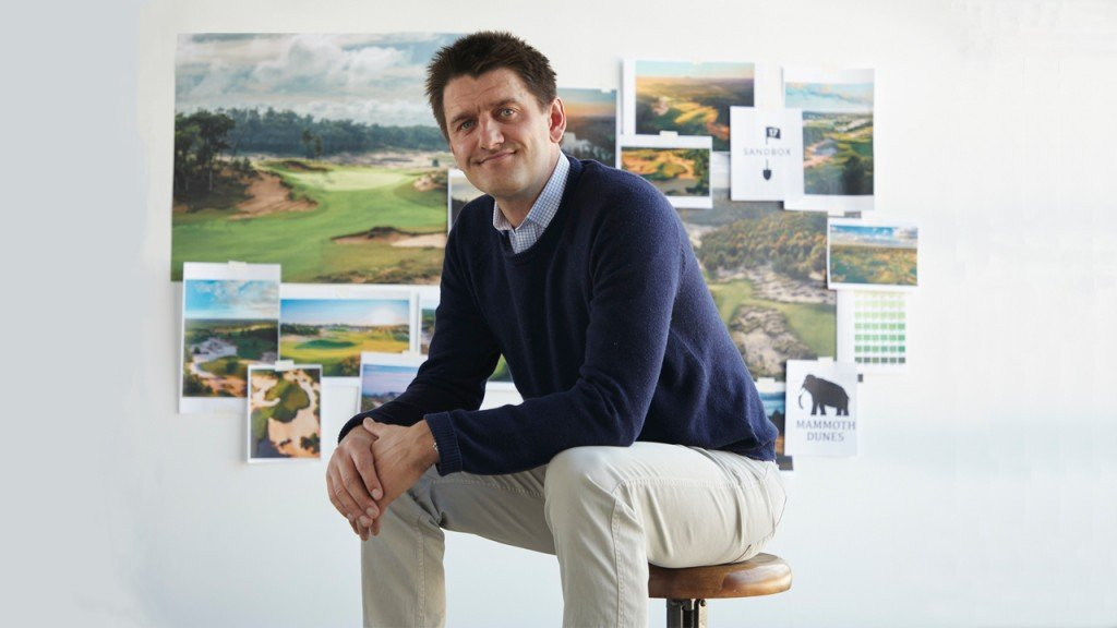 golf course designer Michael keiser sits on a round stool with photos and plans of his courses shown behind him