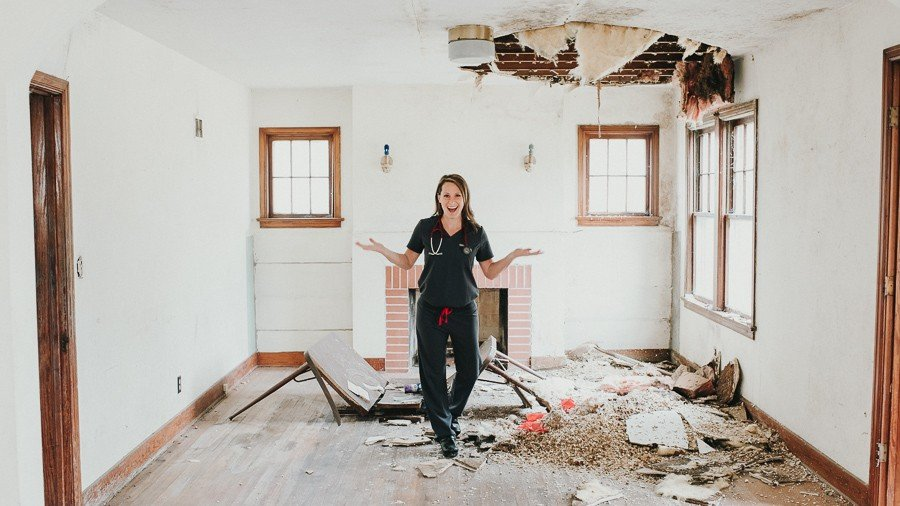 Dr. Amanda Preimesberger stands in scrubs amidst the rubble in an old Verona home she is remodeling for her Direct Primary Care practice