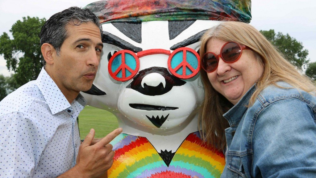 Radio morning co-hosts Jonathan and Kitty stand on either side of a Bucky Badger statue that is dressed like a Madison hippie