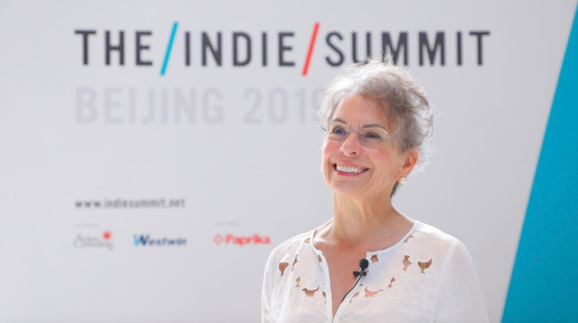 Marketing maven Marsha Lindsay, wearing glasses and dressed in white, stands in front of a background with the words The Indie Summit while speaking at a Beijing conference in 2019.
