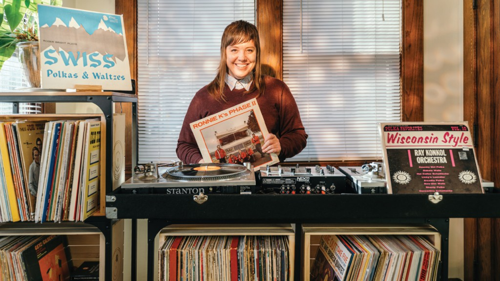 Stacy Harbaugh holding a record in her DJ set up