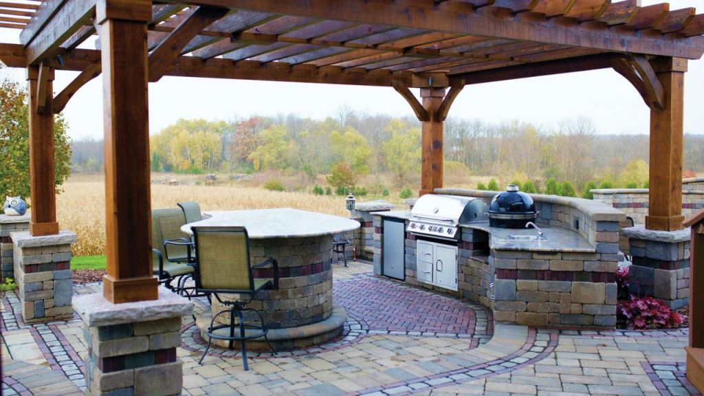 An outdoor brick patio with a grilling area and pub style seating