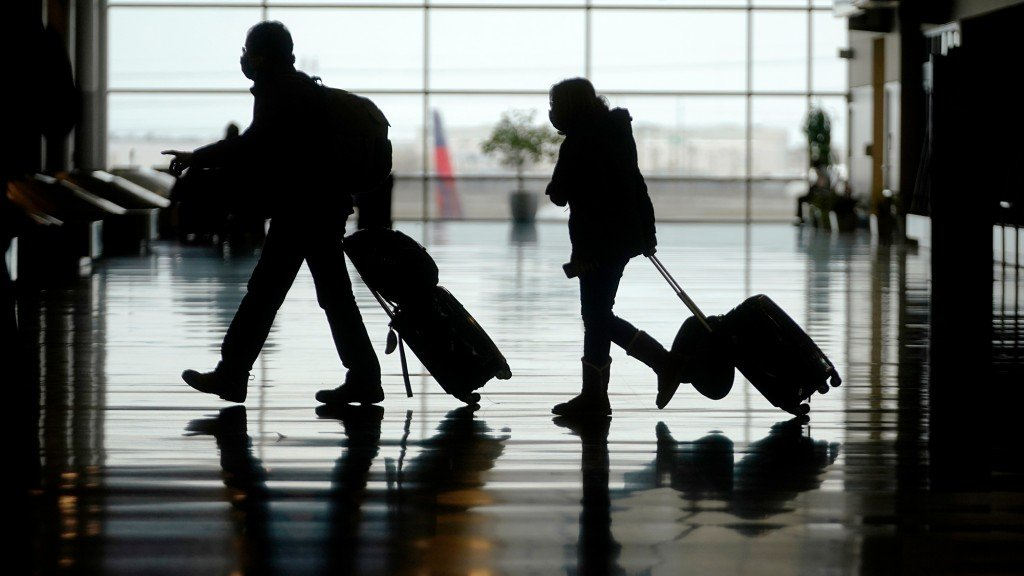 2 passengers walk through airport with suitcases