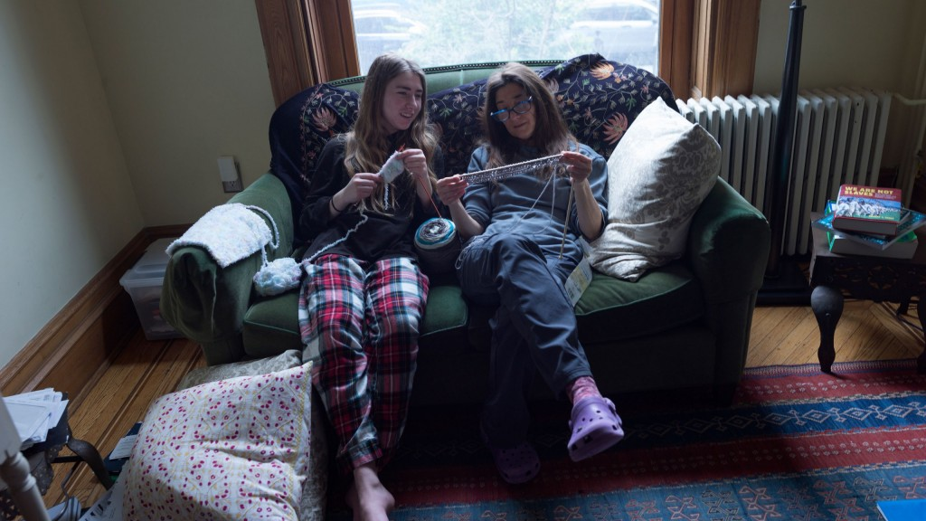 2 girls sit on a couch with a ball of yarn, knitting