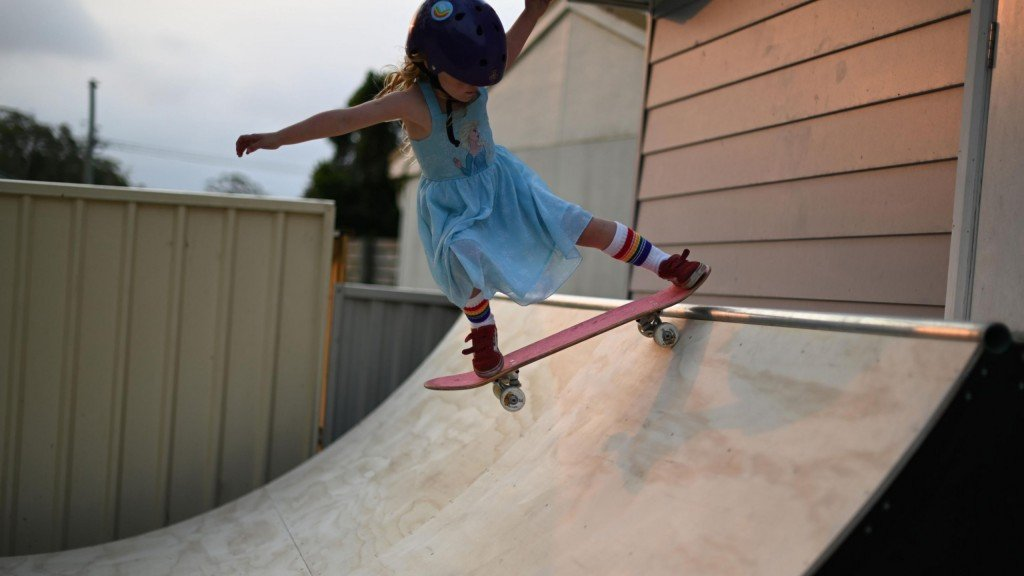 Paige on her skateboard rides down a ramp