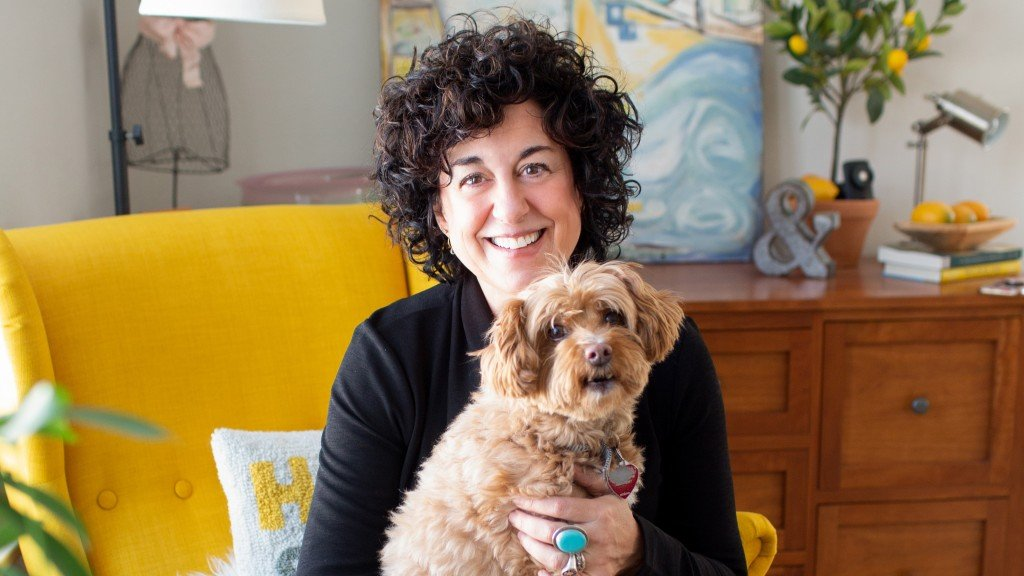 Author Ann Garvin sits in her house on a yellow chair with her dog, Peanut, in her lap.