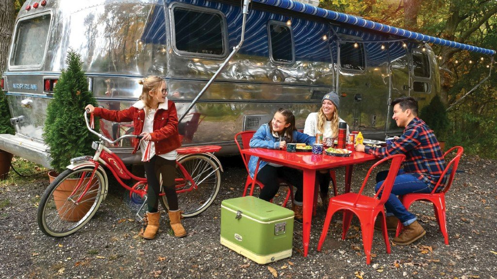 family eating at a table in front of an airstream