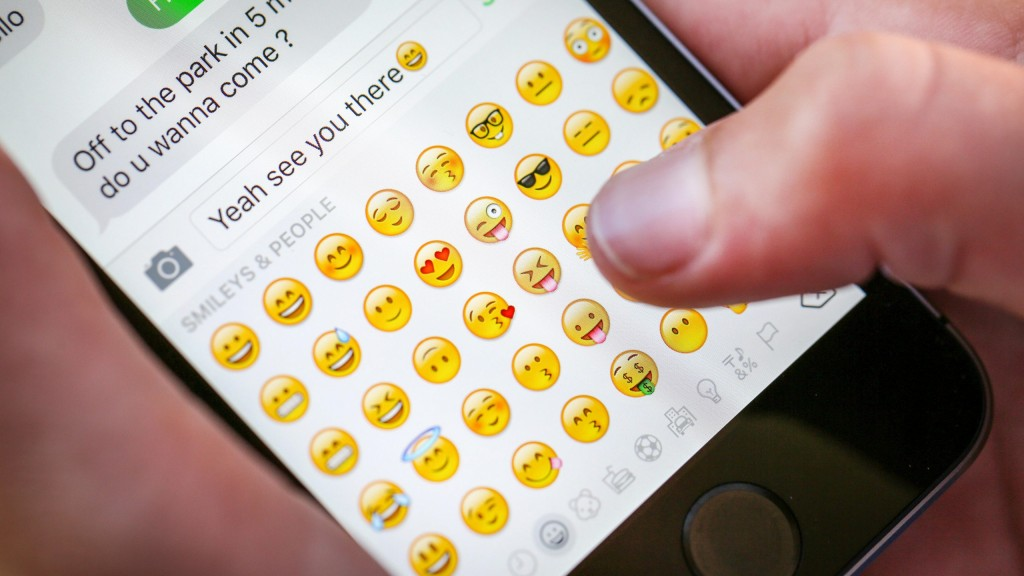 A Teenage Boy Using An Emoji Whilst Texting On His Iphone