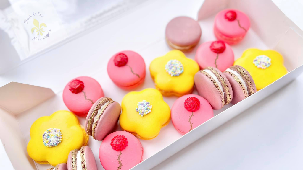 Pink and yellow macarons in a white box