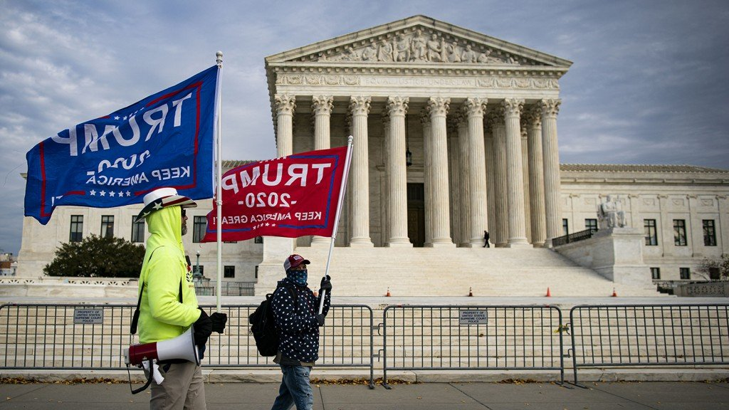 2 men wave Trump flags in front of the Supreme Court.