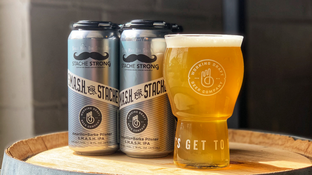 Two cans of Smash For Stache next to a full glass of beer.
