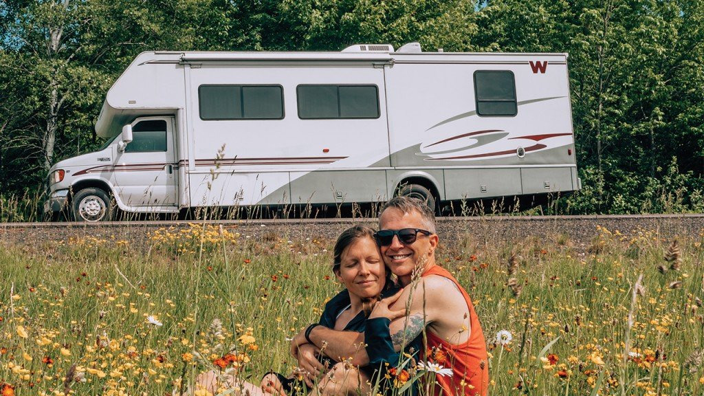 Sarah and Tim sitting in flowers in front of rv
