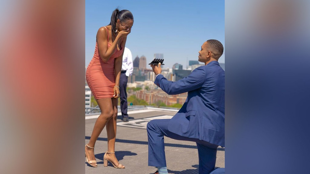 A man on one knee presents 5 rings to the woman standing in front of him