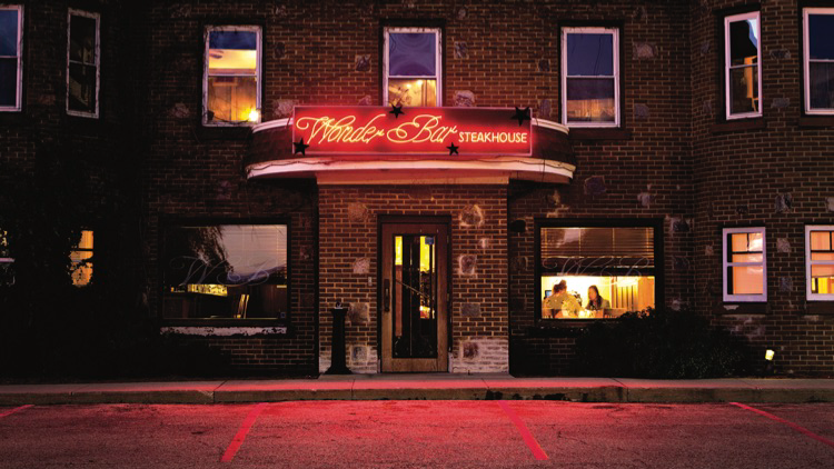 An outdoor shot of the Wonder Bar by night, with its iconic red sign glowing above the entrance and reflected onto the pavement below.