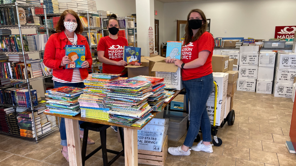Rowan Childs and two Madison Reading Project staff members stand around a table packing up books to donate in the new space on Madison's south side.