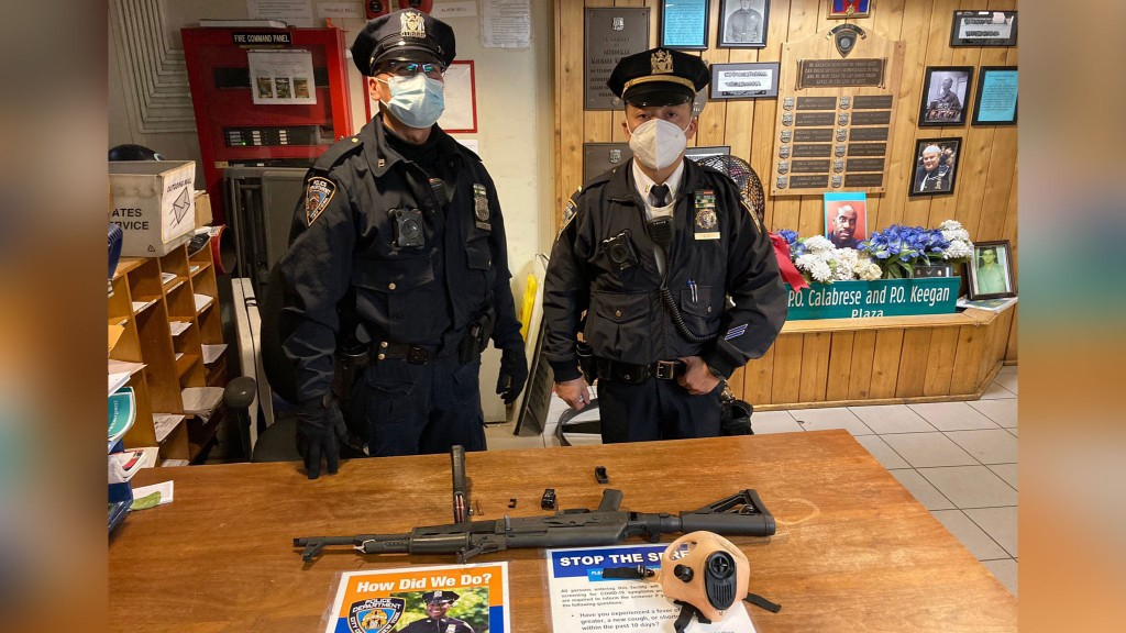 2 police officers stand with confiscated assault rifle