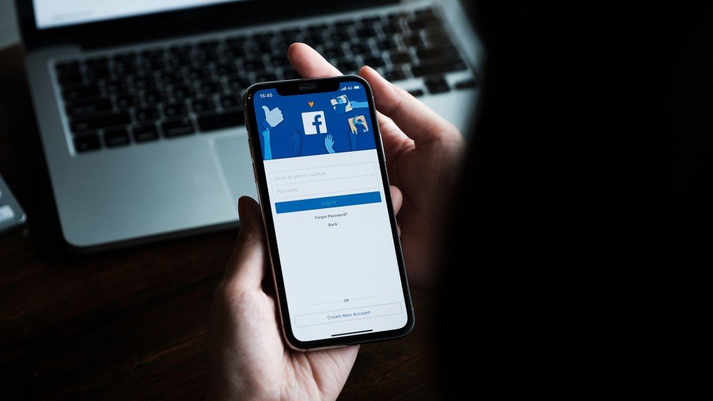 hands hold a cellphone with the Facebook login page on display