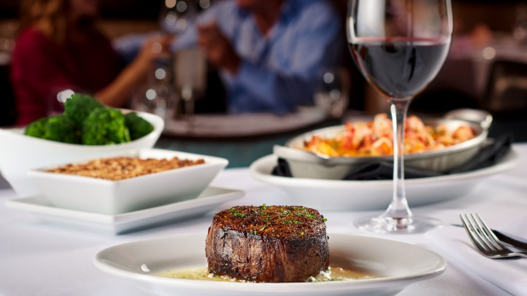 Restaurant Table Setting with Juicy Steak, Wine and sides on a tablecloth.