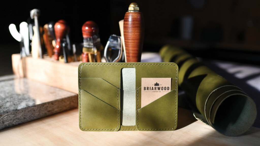 Green leather wallet on a tool bench