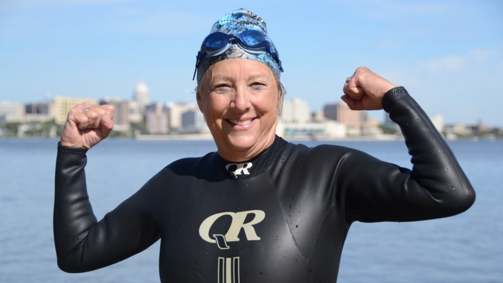 Mary Gooze smiling and flexing muscles in a wet suit in front of a Madison lake