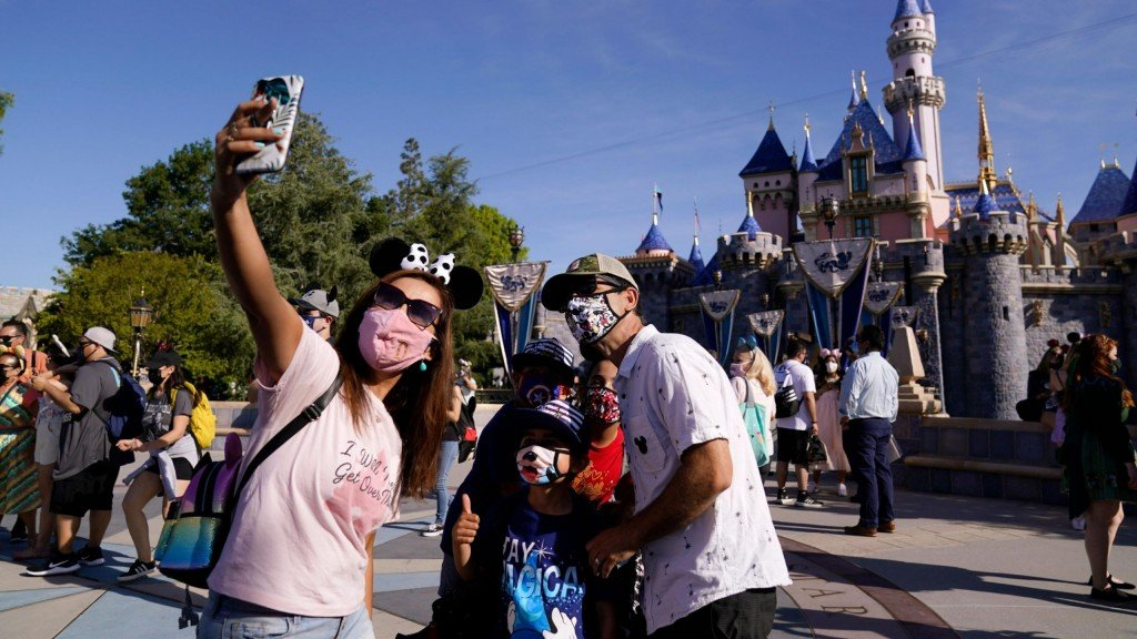 three people in masks take a selfie in front of the disney castle