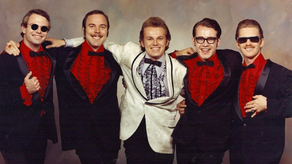 a perhaps 1970s-era photo of the band called Dr Bop And The Headliners, lined up in black and red suits with lead singer Al Craven in a white jacket in the center.