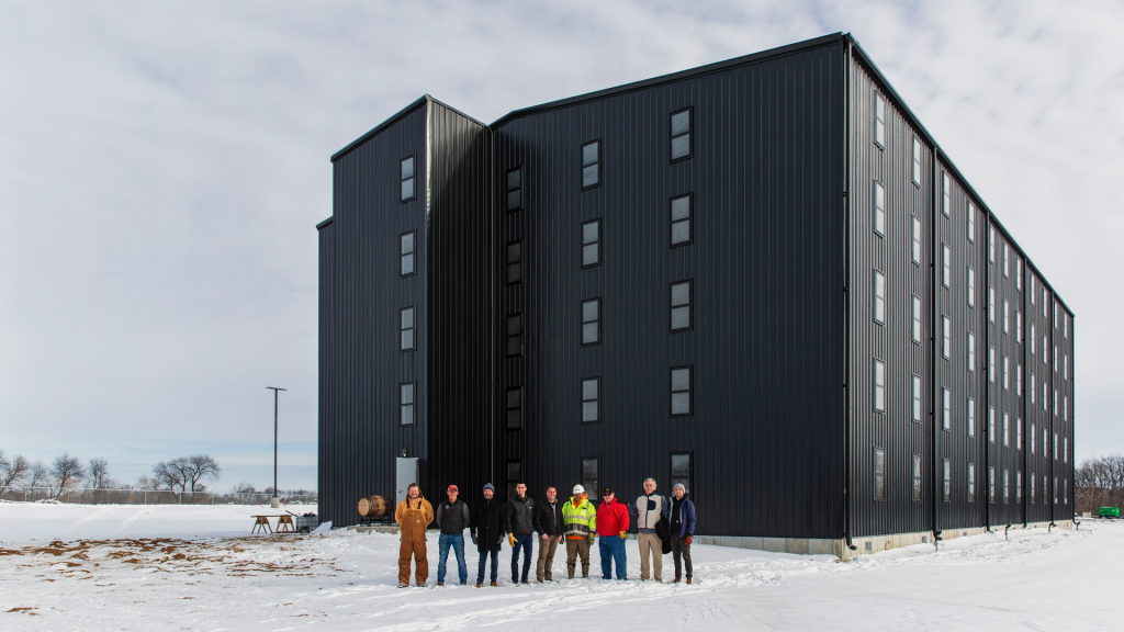 Nine men stand in front of a five-story storage facility.