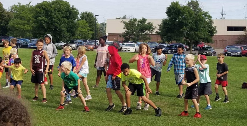 a group of kids playing outside in the grass at Lussier East YMCA of Dane County