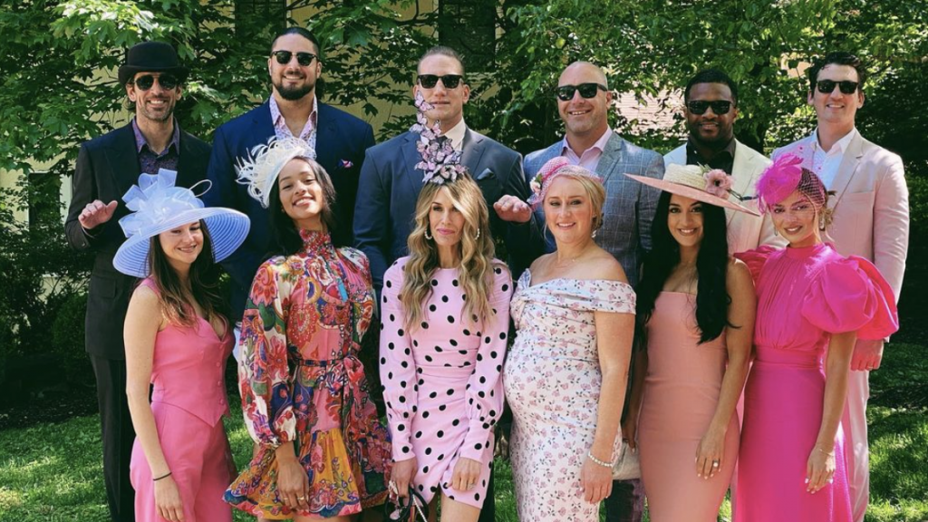 Aaron Rodgers in a top hat smiles with fiancé and teammates