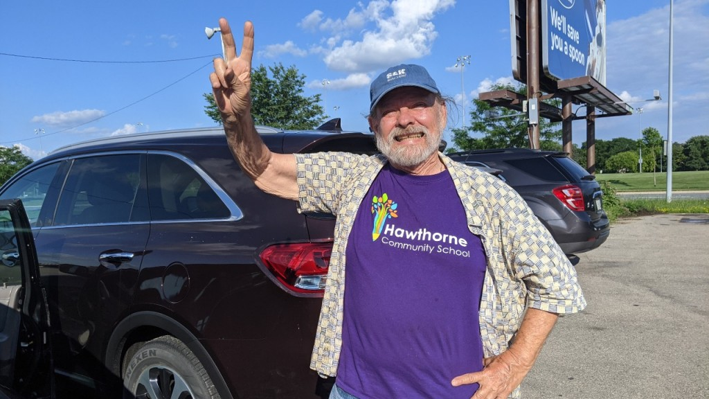 Larry Orr holds up a peace sign and smiles in his Hawthorne t-shirt.