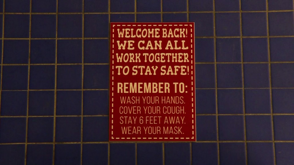 a sign recommending hand washing, mask wearing, and social distancing