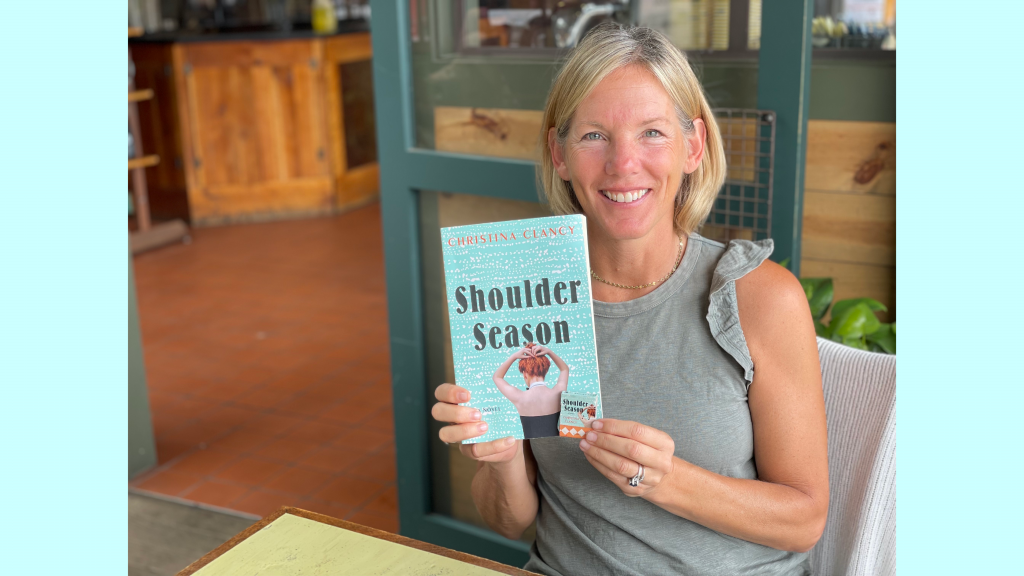 Author Christina Clancy sits at a table at Colectivo Coffee holding up an advance reader copy of her new book Shoulder Season
