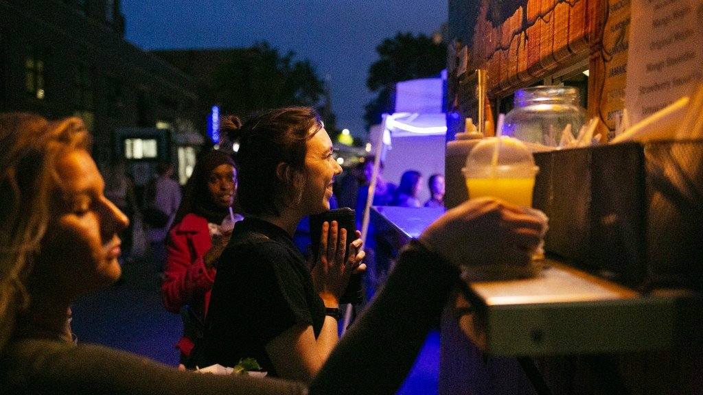 Person walking up to order at a food cart during the Madison Night Market