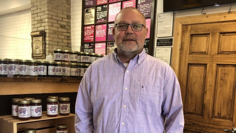 Owner of Peanut Butter & Jelly Deli smiles in front of his nut butters inside his Milwaukee-based shop.