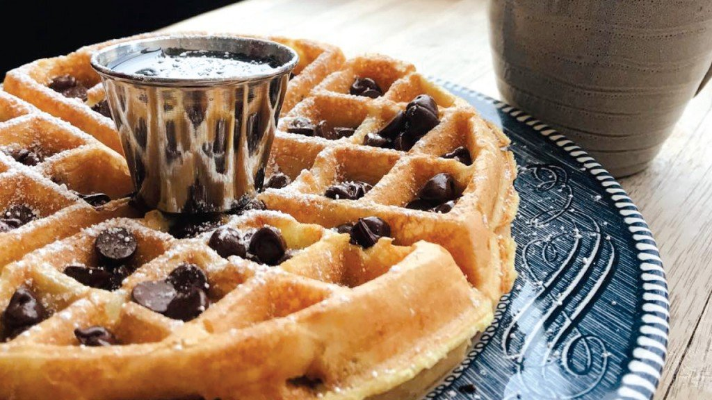waffle on a plate with a cup of syrup